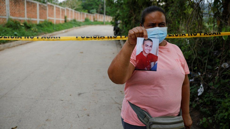 Marleny Barrientos shows a picture of her son who went missing six years ago and is believed to be at the site authorities are excavating
