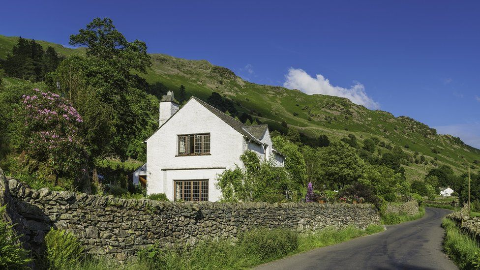 A house in the British countryside next to hills and on a country lane
