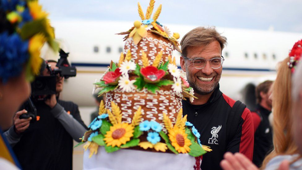 Liverpool manager Jurgen Klopp receiving a gift as he arrives ahead of the UEFA Champions League final at IEV Airport in Kiev