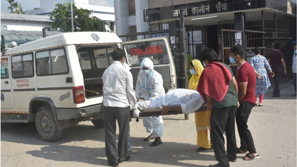 People next to suspected Covid-19 patient seen without PPE gear at Nalanda Medical College and Hospital campus -- designated Covid-19 hospital, on July 22, 2020 in Patna, India.