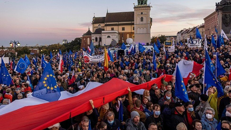 Protesters wave flags at a pro-EU rally in Warsaw