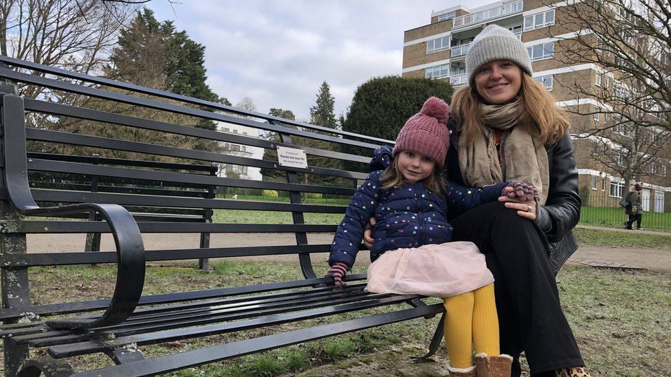 A woman and her young daughter sitting on a park bench with a block of flats in the background