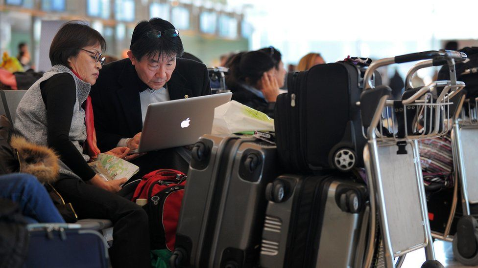 Passengers use their laptop as they wait for their flight
