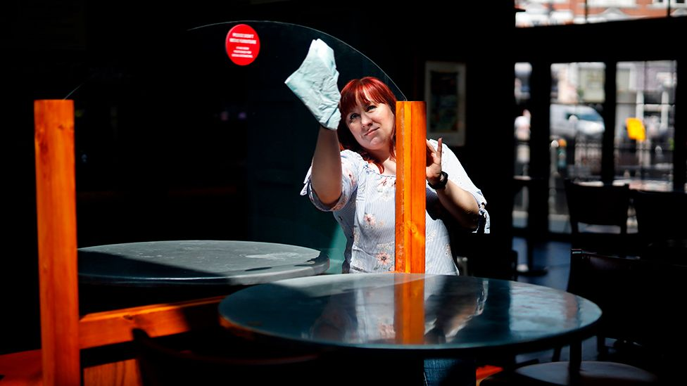 Pub worker cleans screen between tables