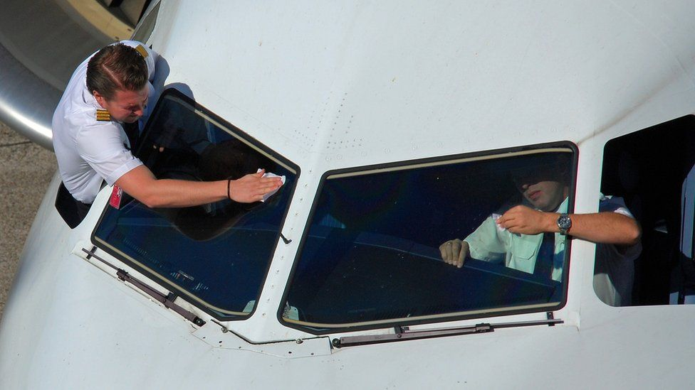 Pilots cleaning the windows of an aeroplane