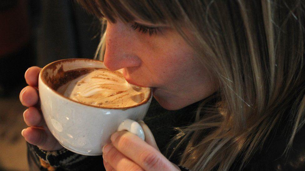 Woman drinking a cappuccino in Berlin, 24 Jan 11