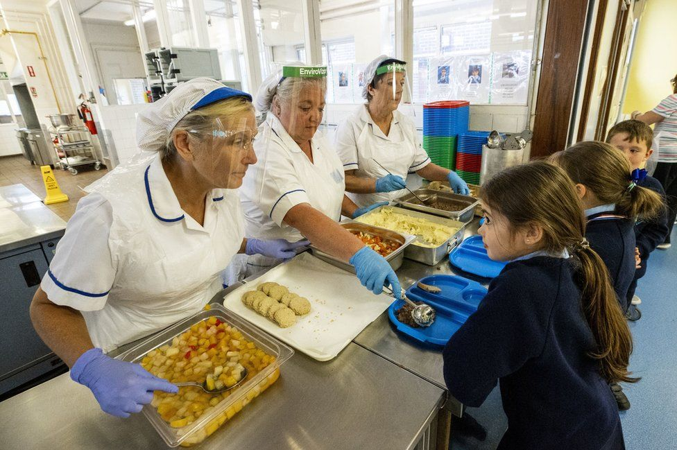 Three dinner-ladies offer lunch to three pupils in a school canteen