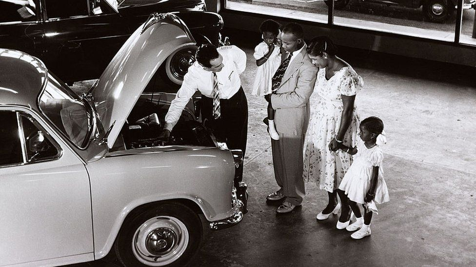 A family in Guyana are shown a Morris car in a showroom, 1958.