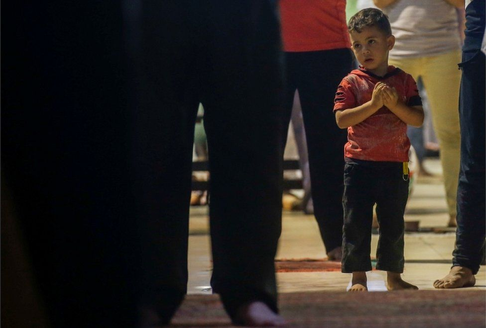 A young boy prays.