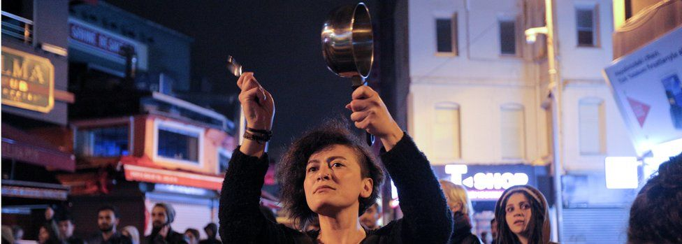 A woman in Istanbul bangs a saucepan to protest against the referendum result