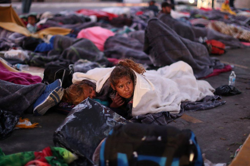 Members of a caravan from Central America trying to reach the United States sleep under a road bridge next to the US-Mexico border in Tijuana, Mexico, 23 November