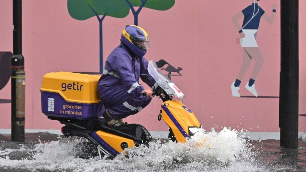 A motorcyclist drives through deep water on a flooded road in The Nine Elms district of London