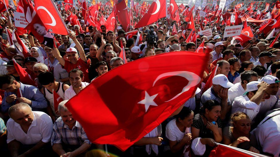 "A supporter of the Republican People's Party, or CHP, waves a Turkish flag bearing a portrait of Mustafa Kemal Ataturk, the founder of modern Turkey, during a ""Republic and Democracy Rally"" at Taksim square in central Istanbul, Sunday, 24 July 2016"