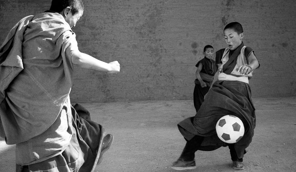 Two young monks play football while a third watches
