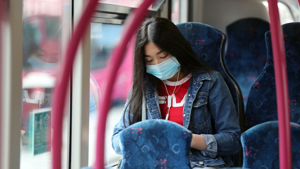 Woman on a Translink bus wearing a compulsory facemask.