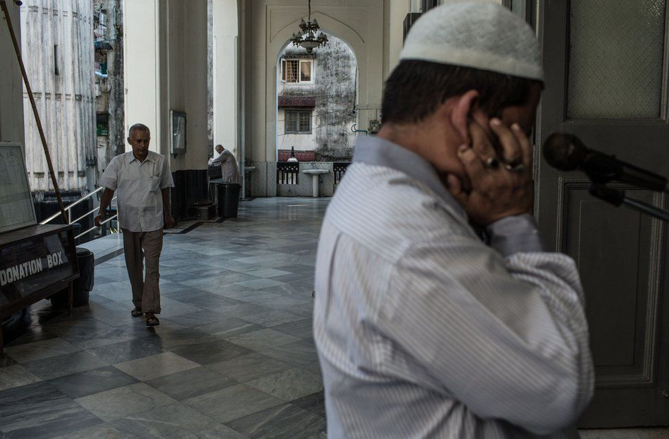 Farooq plugs his ears while issuing the call to prayer just after midday - known as the Zuhr prayer - at the Shia Mughal Mosque in downtown Yangon, Myanmar, November 19, 2015