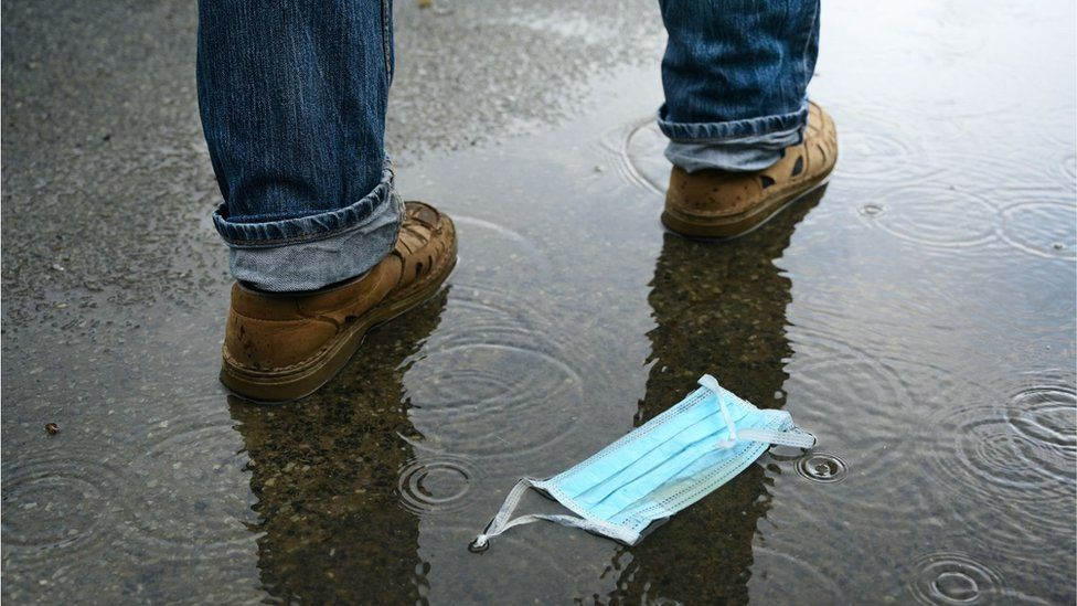 A man walks by a discarded face mask lying in a puddle