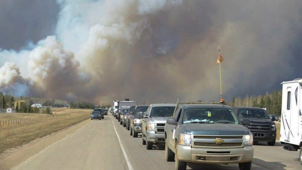 Smoke fills the air as people drive on a road in Fort McMurray, Alberta, Tuesday, May 3, 2016.