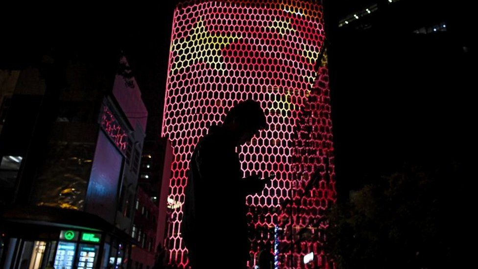 Person on smart phone in front of Chinese flag projection