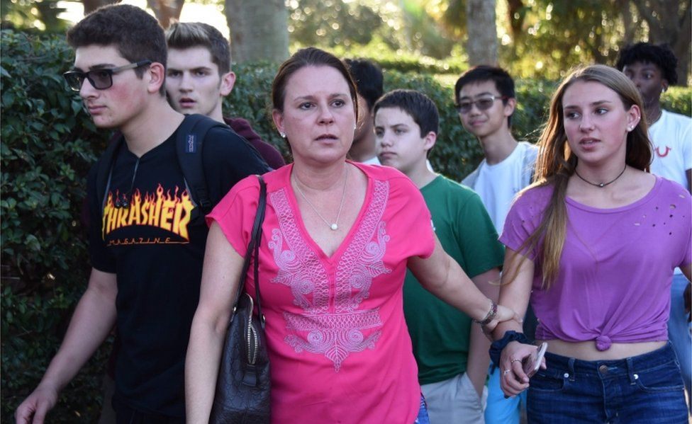Students and adults holding hands leave the scene of Marjory Stoneman Douglas High School.