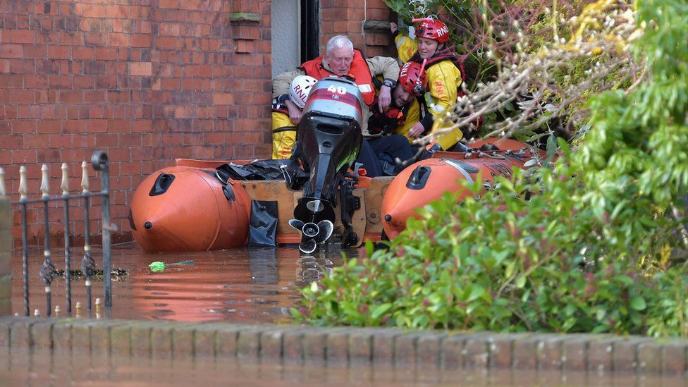 A man is helped from his home in Carlisle by rescue teams
