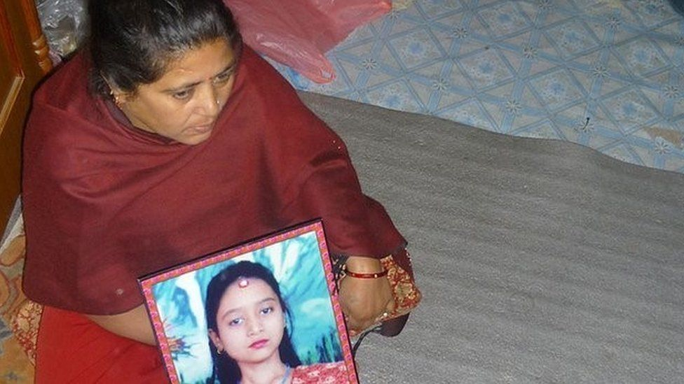 Dewi Sunuwar holds a picture of her daughter who was tortured and killed