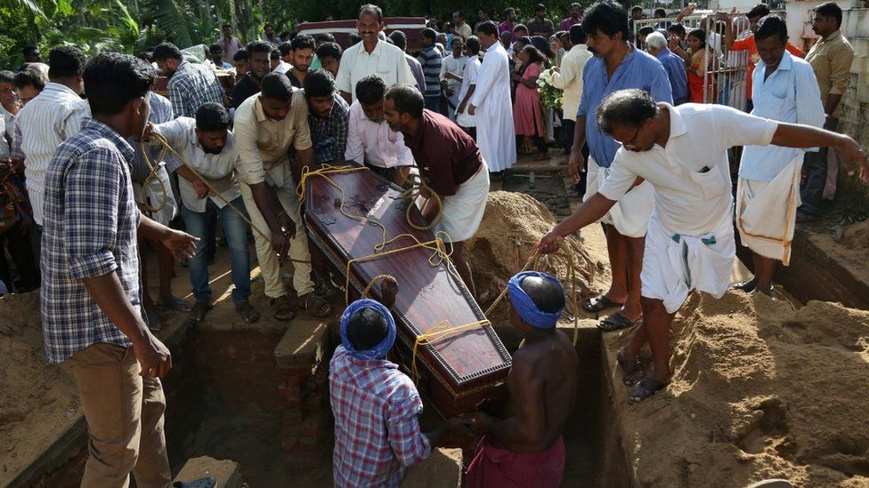 Men are lowering a coffin into a grave