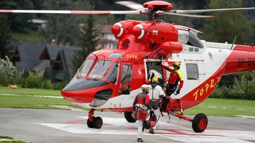 Mountain rescue team (TOPR) members board a helicopter in Poland August 18