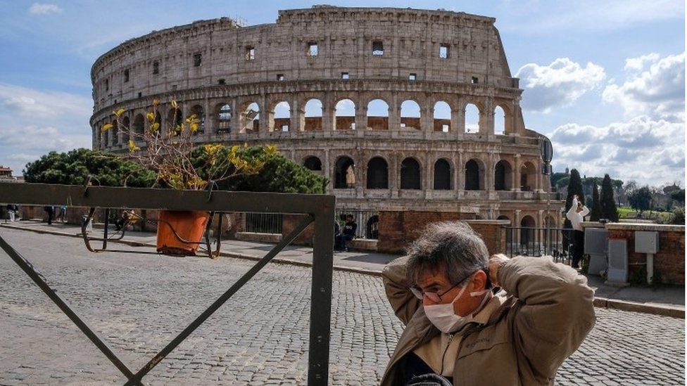 A tourist wearing a mask sits at the tables of a restaurant in front of the Coliseum, in Rome, Italy, 9 March 2020.