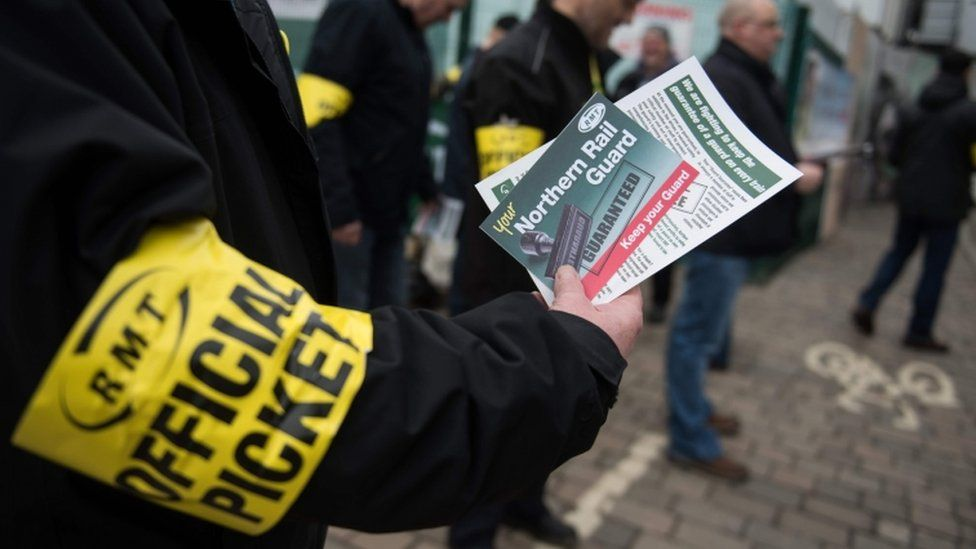 Members of rail staff taking industrial action hand out leaflets giving details of their situation to passengers