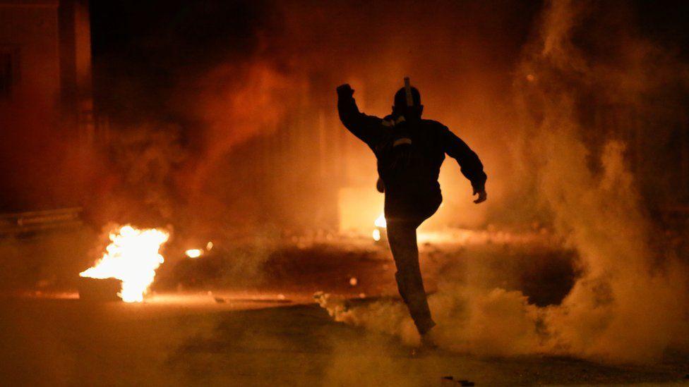 A demonstrator kicks a tear gas canister