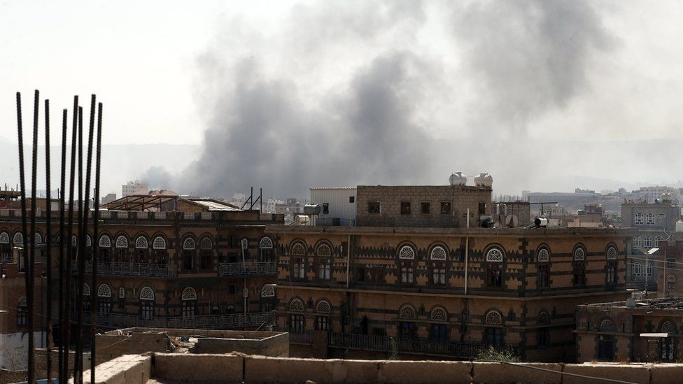 "Smoke billows above a neighbourhood following Saudi-led airstrikes targeting positions in Sana""a, Yemen"