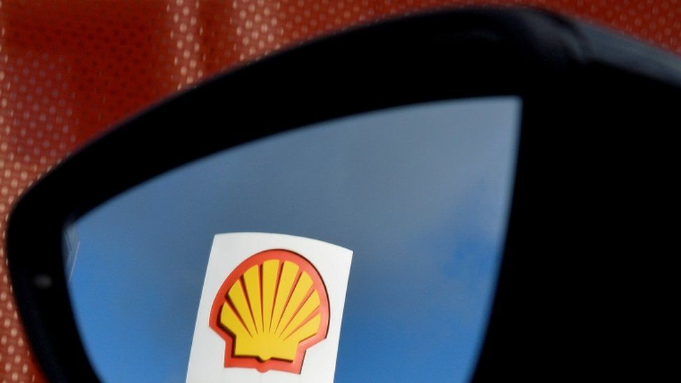 Shell logo is reflected in a car mirror