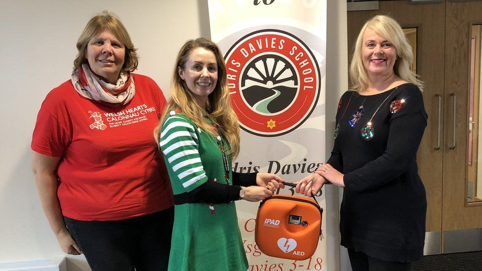 A defibrillator presentation at Idris Davies School. There are three women in the photograph. The second and third are passing a defribilator to one another).