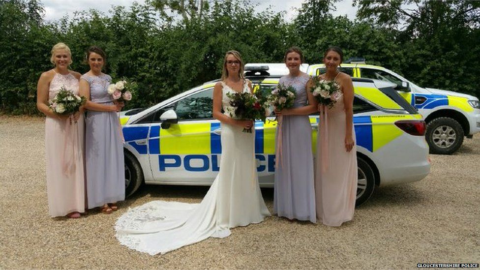 Bridal party posing by police cars