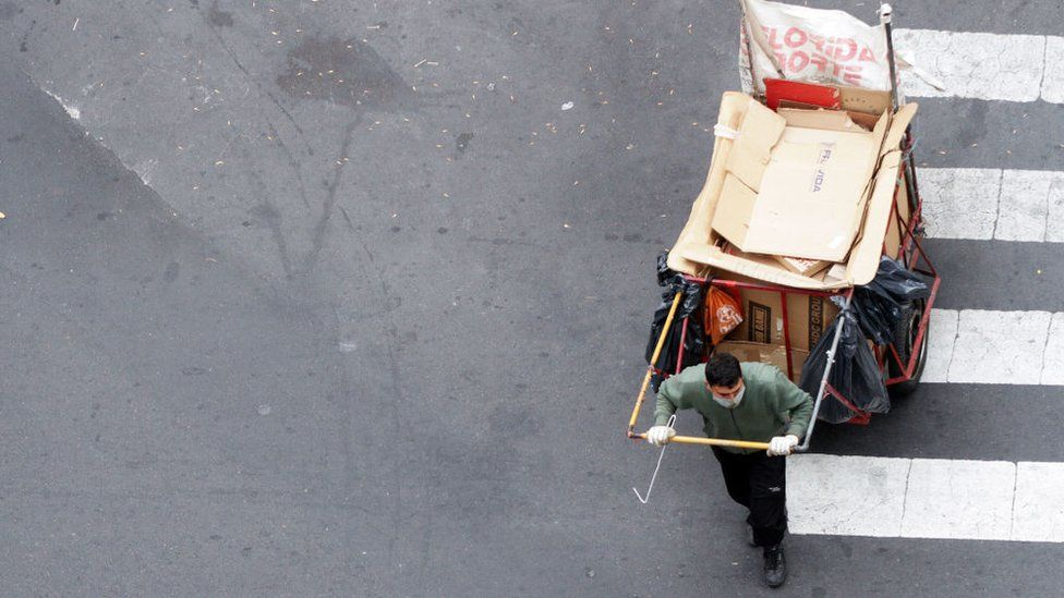 A waste worker is collecting rubbish bags along a street in Buenos Aires