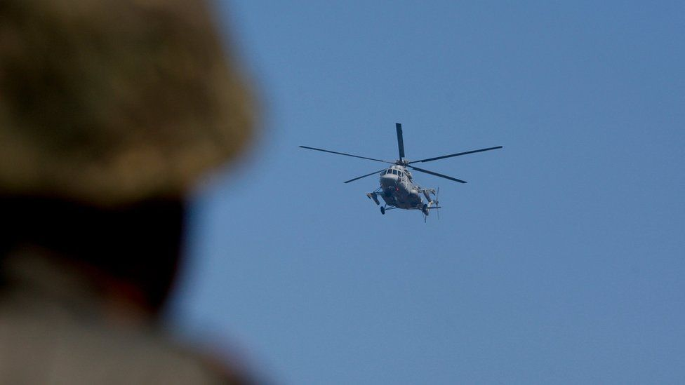 An Indian helicopter flies above the base in Pathankot