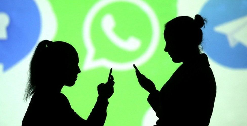 Two women are pictured silhouetted while using their mobile phones