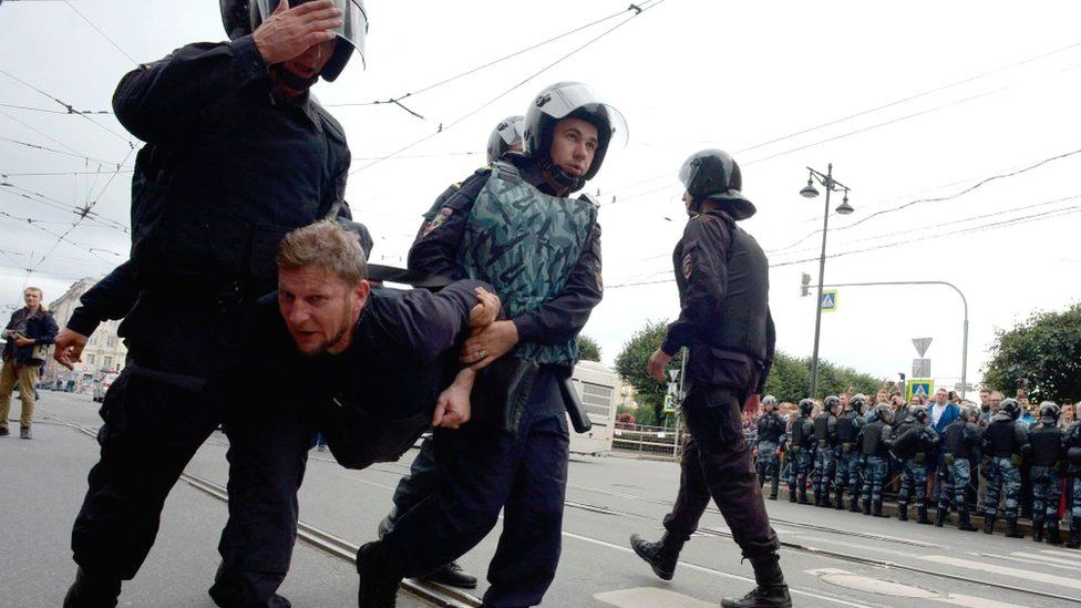 A protestor is carried away by police in St Petersburg