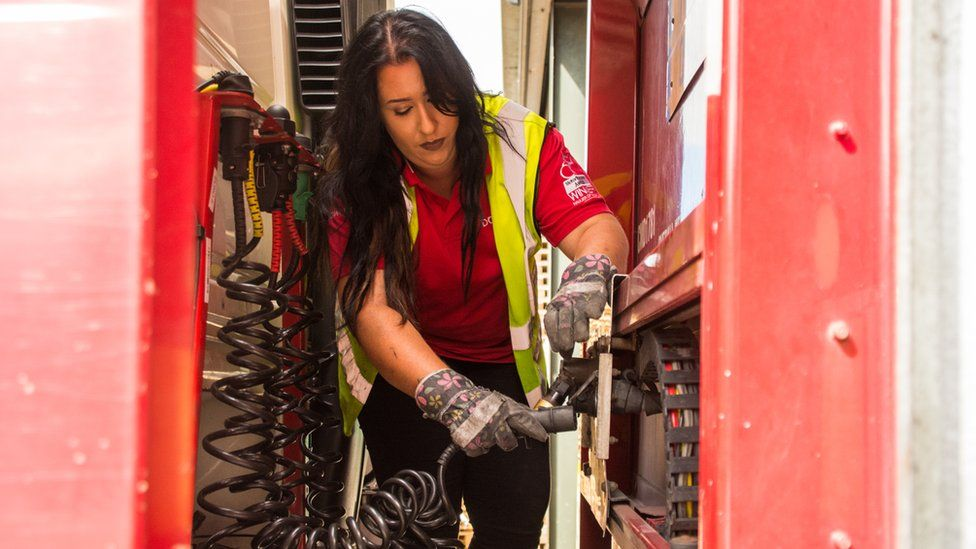 Leonie John attaching hydraulic cables between her cab and trailer