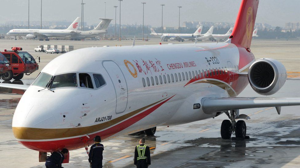 Chengdu Airlines crew members celebrate the arrival of the ARJ21 jet at the Shuangliu International Airport on 29 November 2015