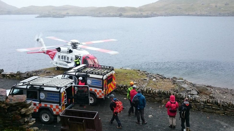 Llanberis Mountain Rescue safely stretcher a fallen walker to the coastguard helicopter below the summit of Snowdon