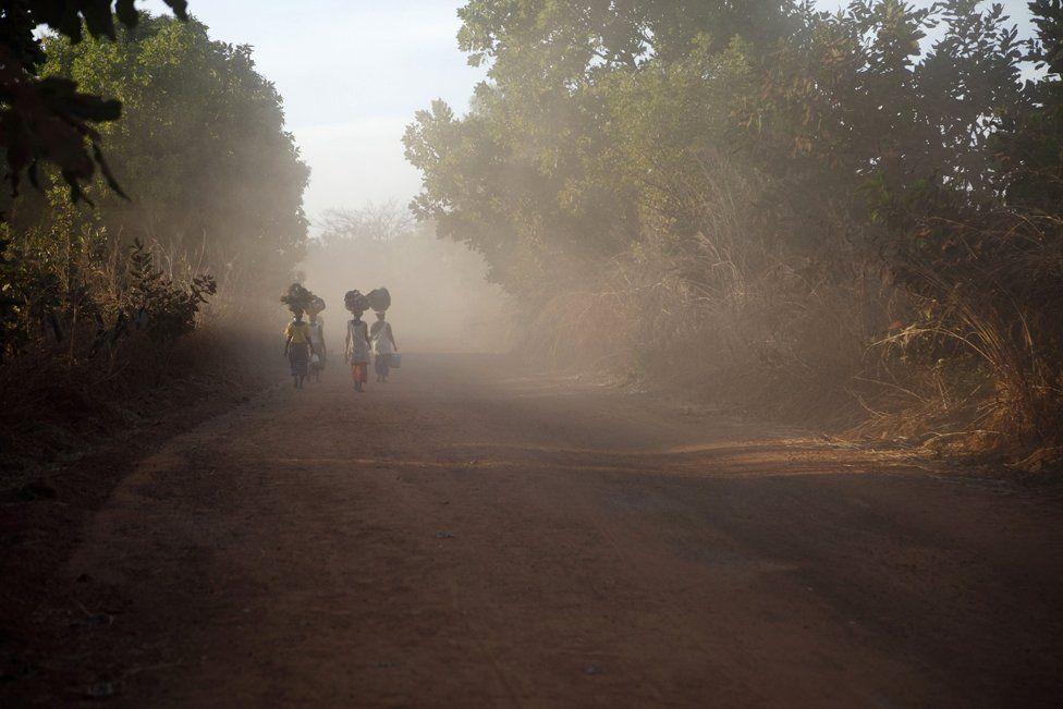 Women walk along a dust road to a market, Gambia