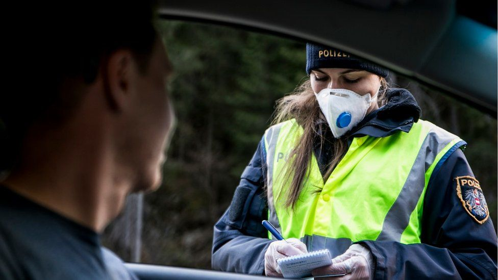 A police officer at a roadblock asks the driver of a car driving out of the Panznautal valley for a drive through permission following the imposition of a quarantine due to the coronavirus on March 14, 2020 near Ischgl, Austria