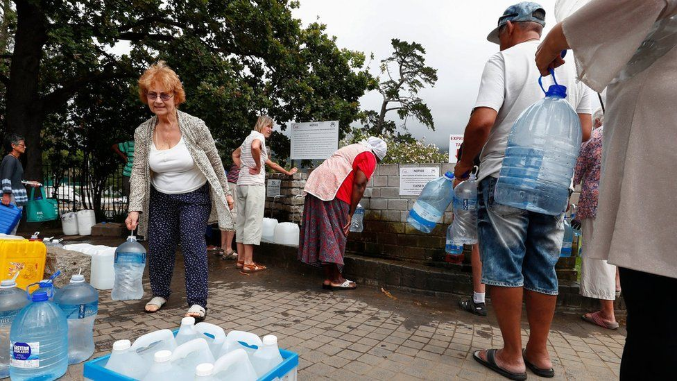 People collect water in Cape Town at a spring