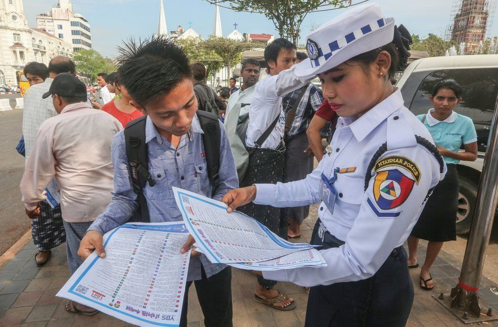 Myanmar traffic police women helping a boy who got lose in his route to going home at the bus stop of Central Yangon, in front of City Hall on 18 January 2017.