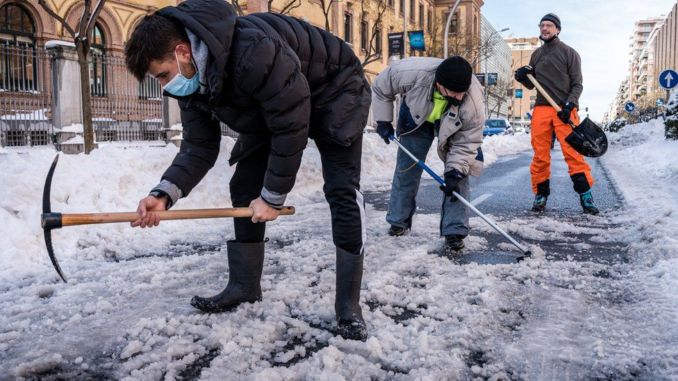 Neighbours clearing the snow in the streets that connect with the Gregorio Marañon Hospital in Madrid