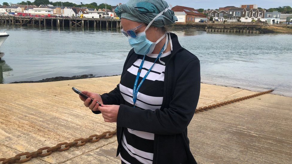 UK National Health Service employee Anni Adams looks at new NHS app to trace contacts with people potentially infected with the coronavirus disease (COVID-19) being trialled on Isle of Wight,