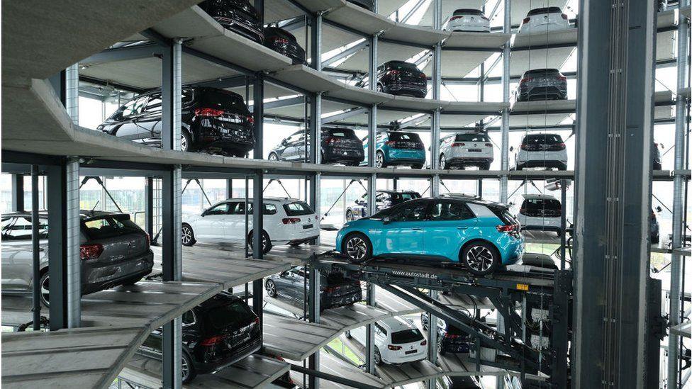 Un automóvil eléctrico Volkswagen ID.3 se encuentra en una plataforma de ascensor dentro de una de las torres gemelas utilizadas como almacenamiento en las instalaciones promocionales de Autostadt junto a la fábrica de Volkswagen.