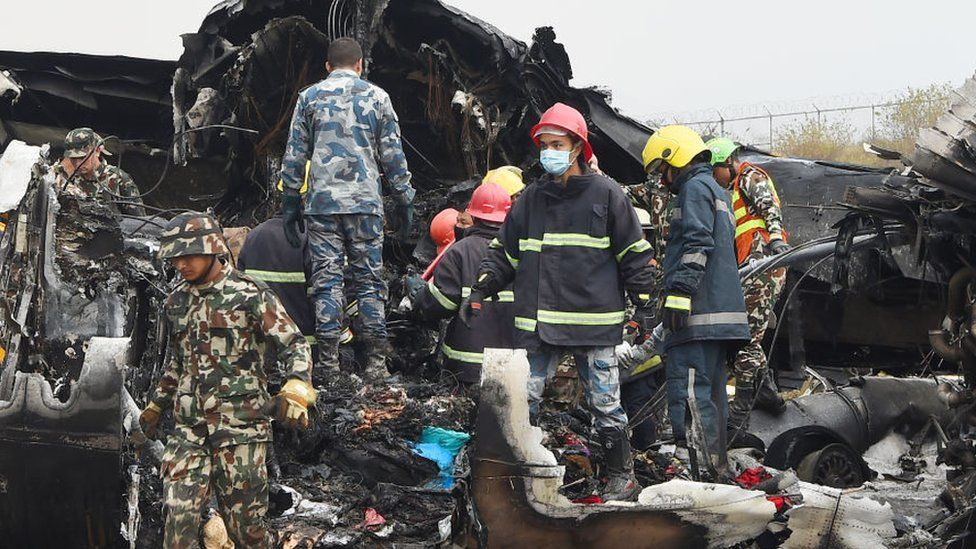 Nepali rescue workers gather around the debris of an airplane